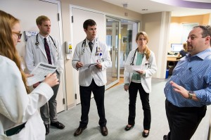 Josh Medow, right, medical director of the Neurocritical Intensive Care Unit at UW Hospital and Clinics, discusses a patient's progress with medical students during the group's floor rounds. CREDIT: Jeff Miller/UW-Madison